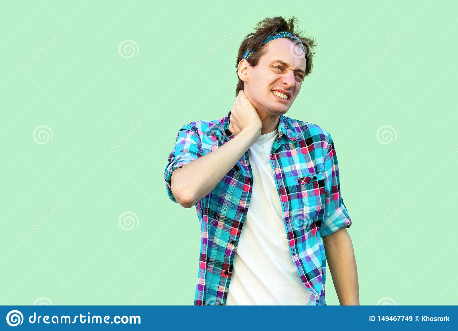 Hals oder R?ckenschmerzen Portr?t des traurigen verletzten jungen Mannes in der zuf?lligen blauen karierten Hemd- und Stirnbandst