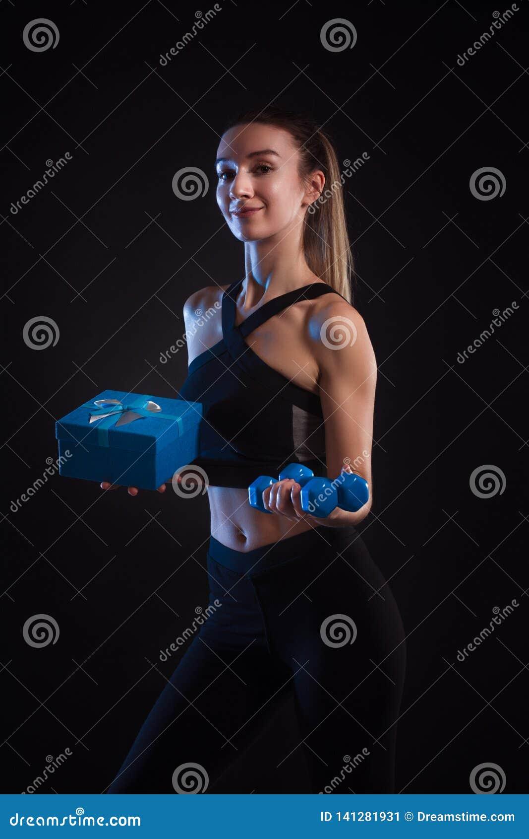 Haltères et boîte-cadeau se tenants blonds sportifs dans des ses mains