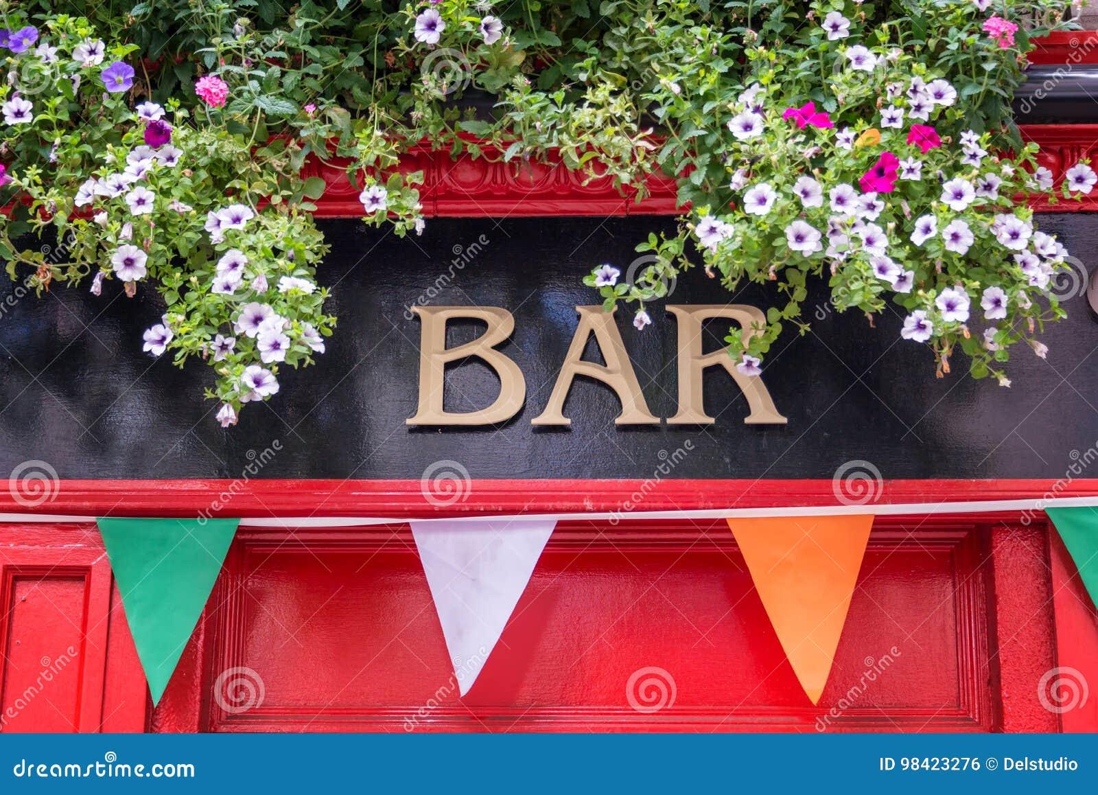 Halten Sie Zeichen mit Blumen und irische Flaggenfarben, irisches Kneipenkonzept in Dublin Ireland ab