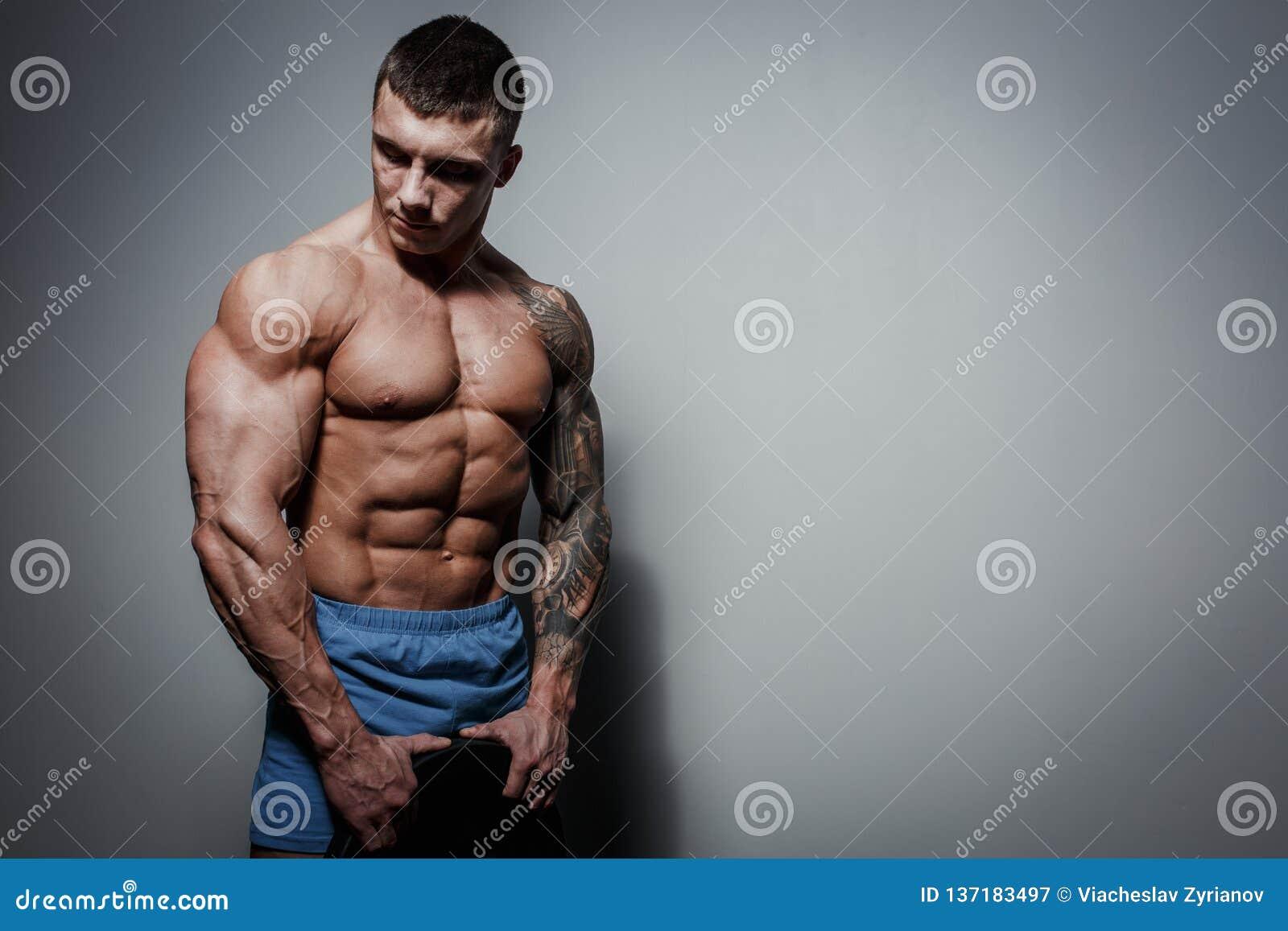 Halterofilista atlético do atleta do homem bombeado com grande corpo muscled no fundo cinzento