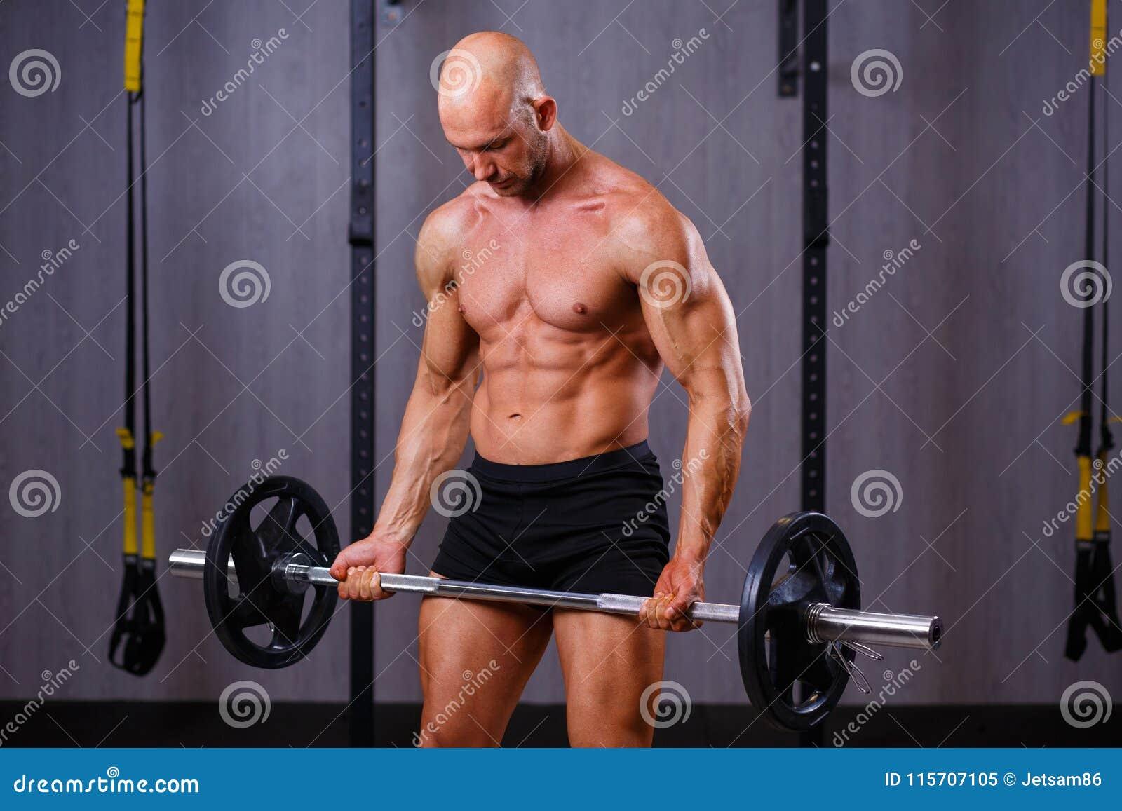 Halterofilista calvo rasgado forte do homem que dá certo com o barbell em g