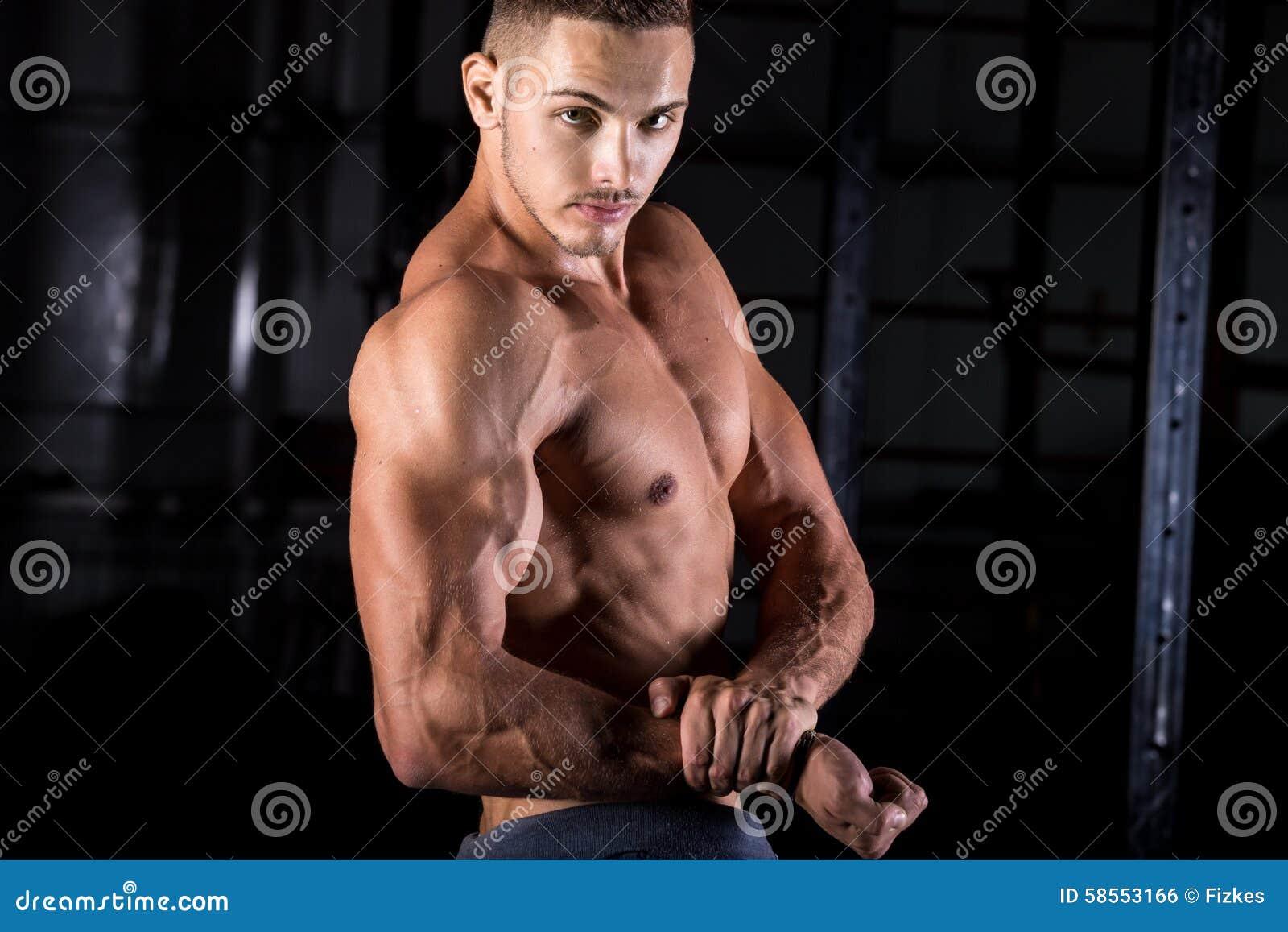 Halterofilista novo que mostra o bíceps forte