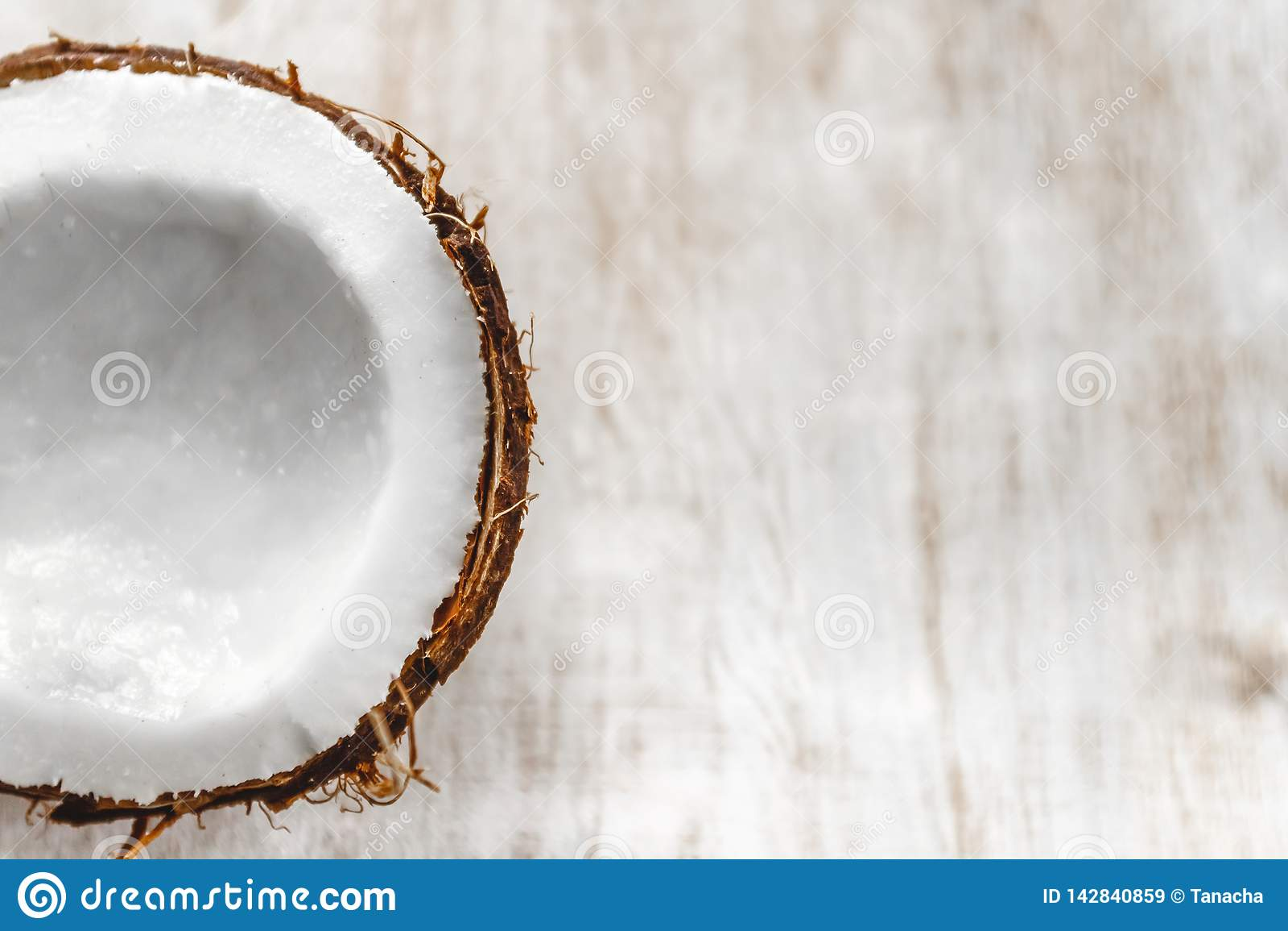 Halv kokosn?t p? en ljus vit tr?bakgrund, closeup Top besk?dar