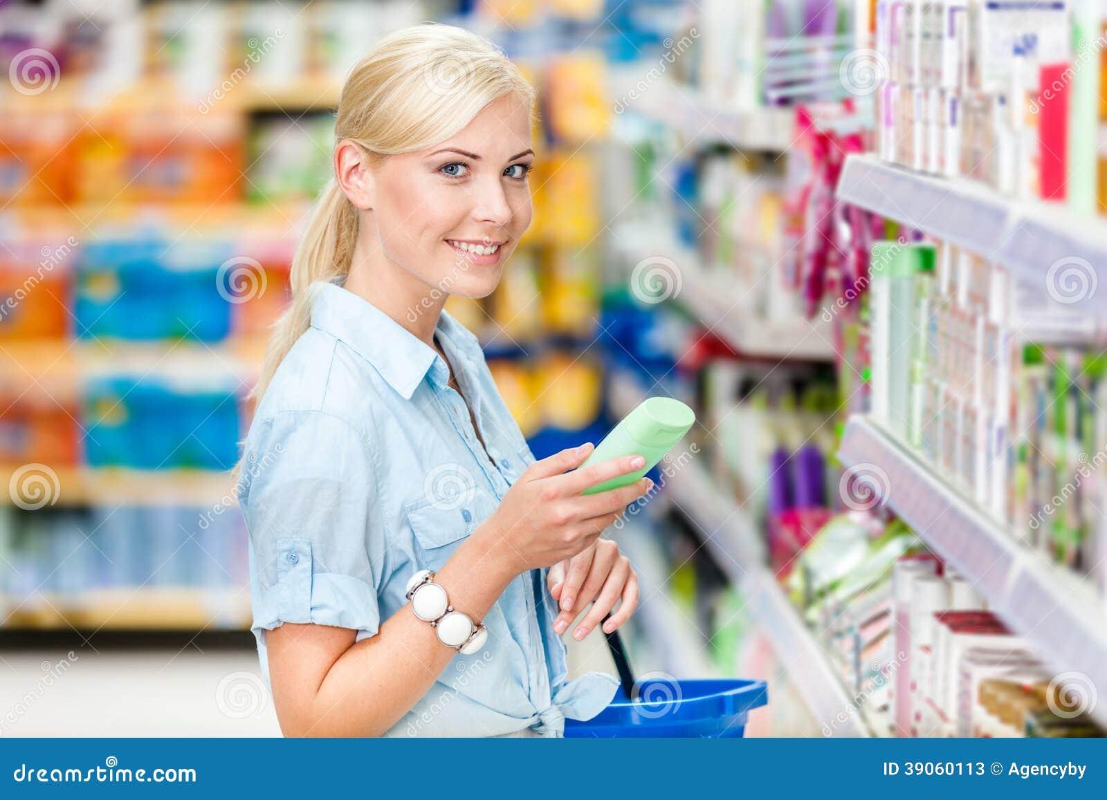 Halv längdstående av flickan på shoppa som väljer skönhetsmedel