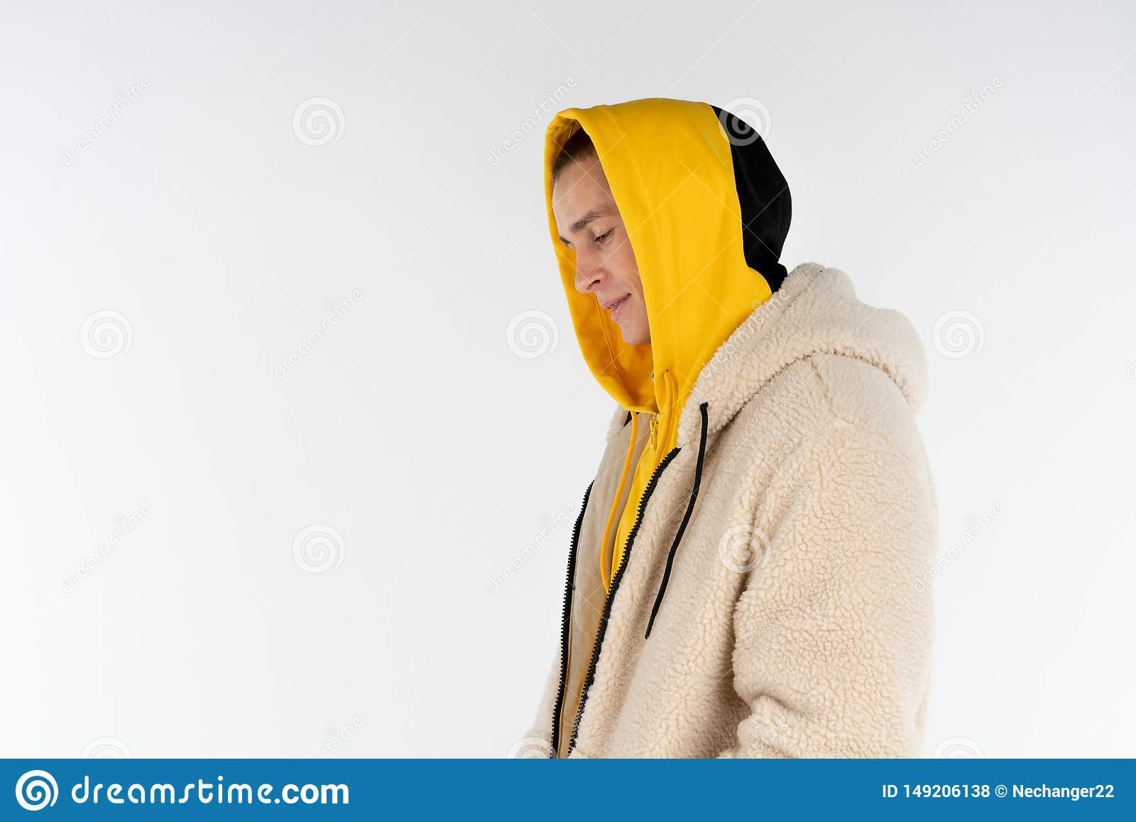 Halv l?ngdst?ende av den unga upprivna olyckliga mannen som b?r gult hoodieanseende mot vit bakgrund, copyspace f?r