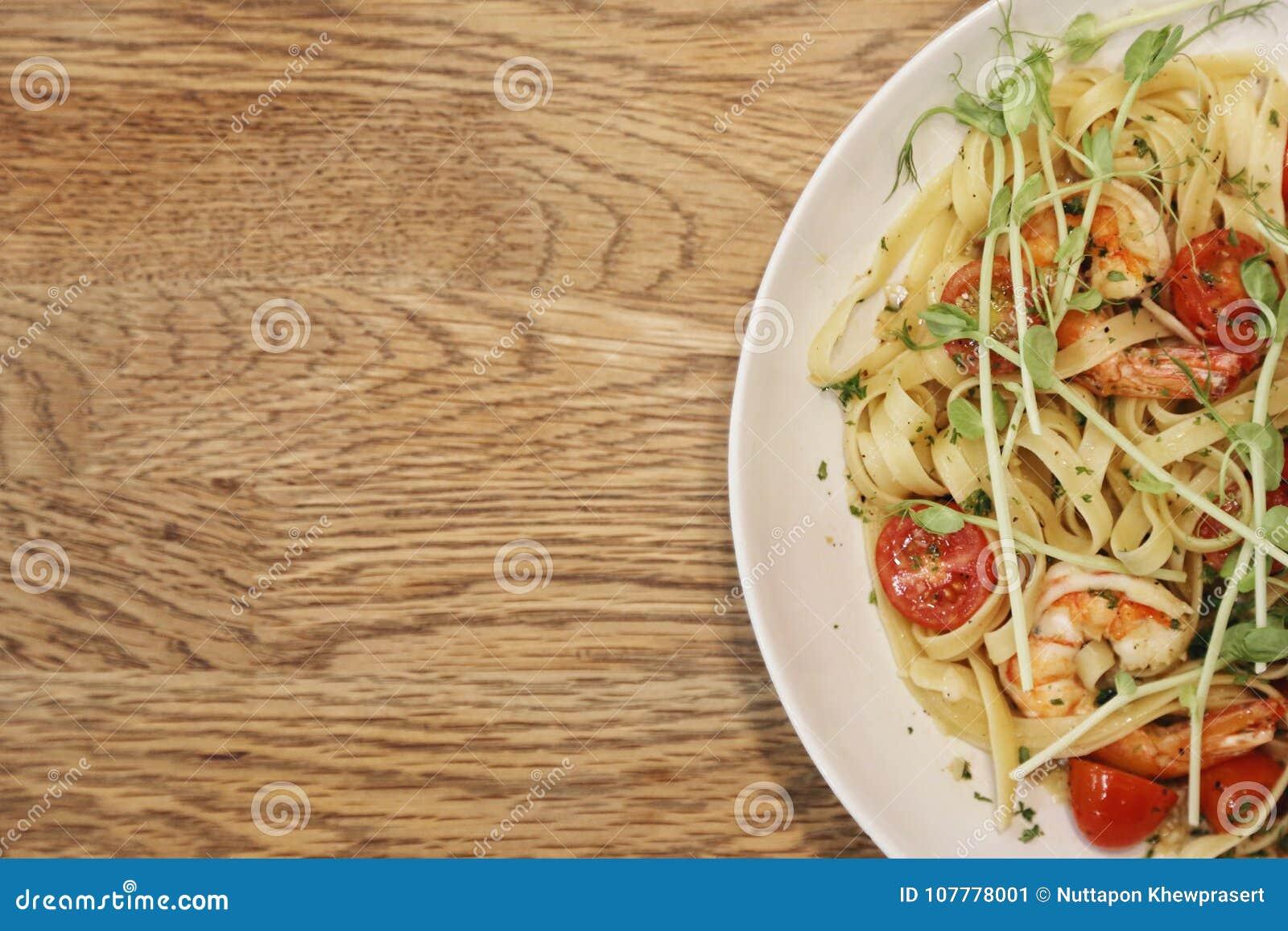 Halva av en vit maträtt med räkascampi och linguine in på en wood tabell från bästa sikt