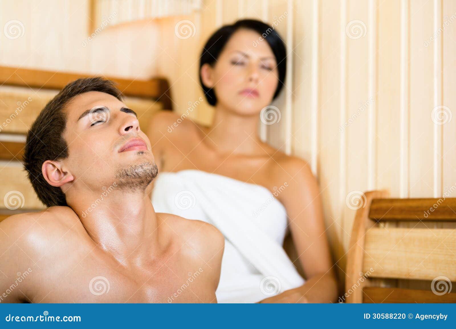 Halva-naken man och flicka som kopplar av i bastu