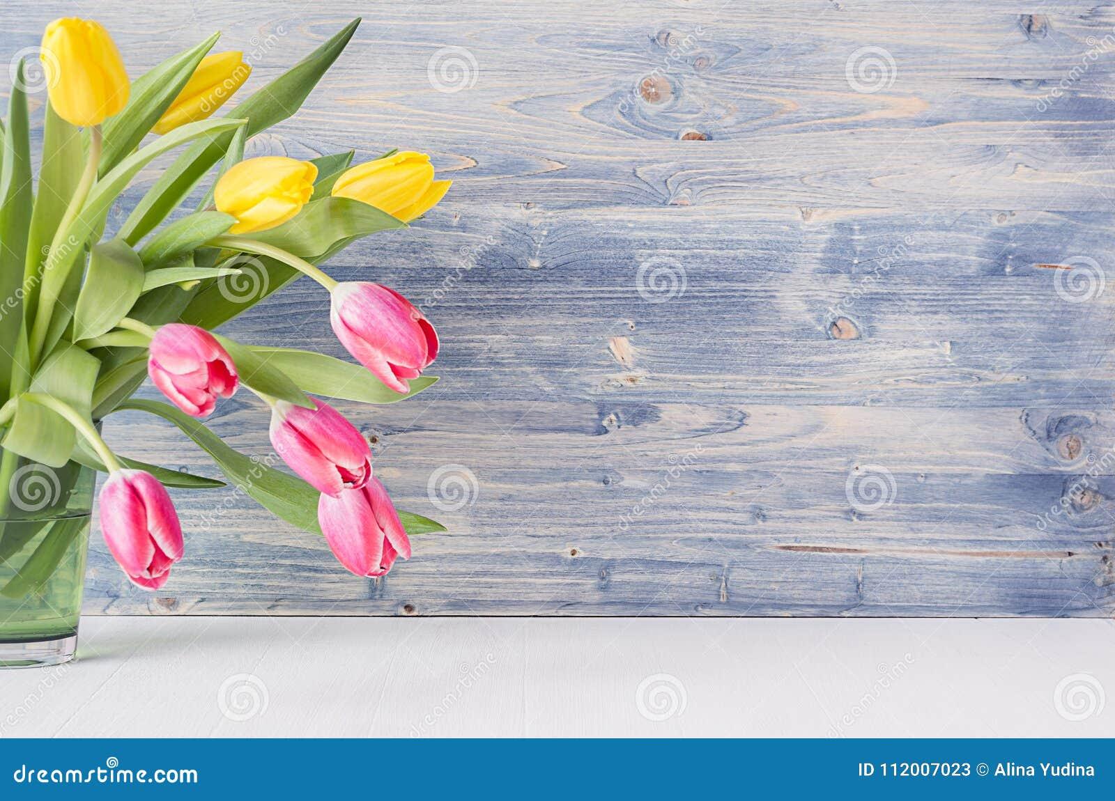 Halve boeket rode en gele tulpen in groene glasvaas op blauwe sjofele houten achtergrond met exemplaarruimte Het huisdecor van de
