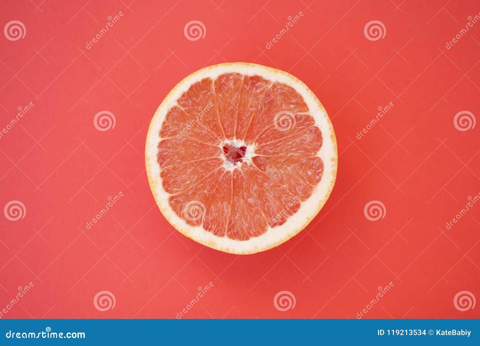 Halved grapefruit on red background.