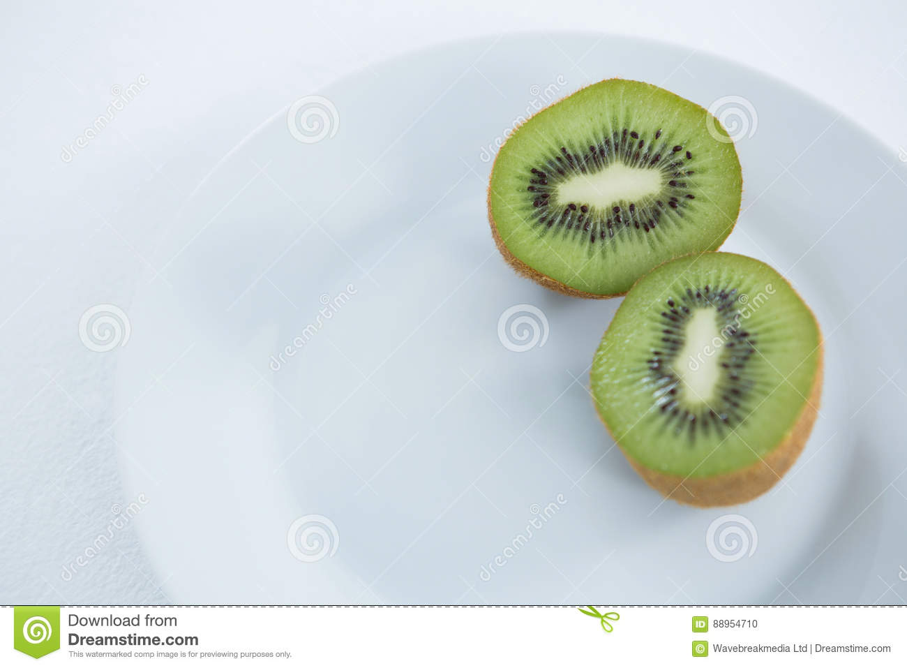 Halved kiwis in plate on white background
