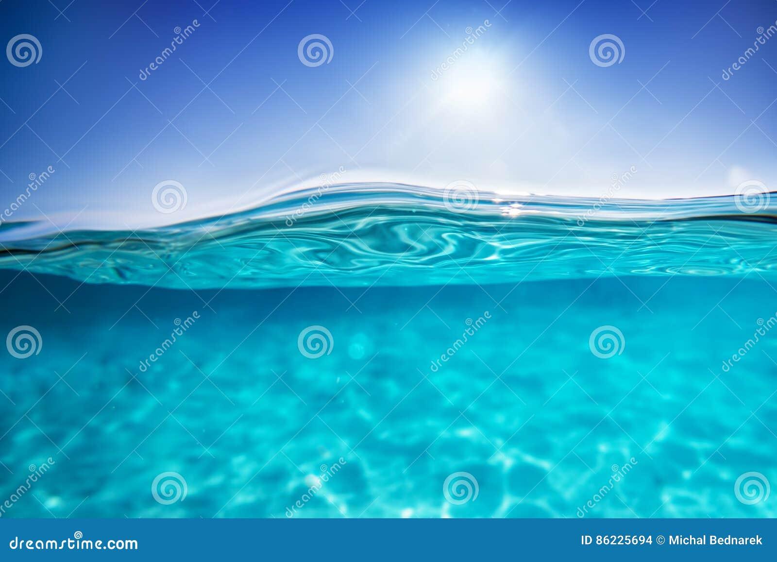 Halvt undervattens- skott, frikändvatten och solig blå himmel tropiskt hav
