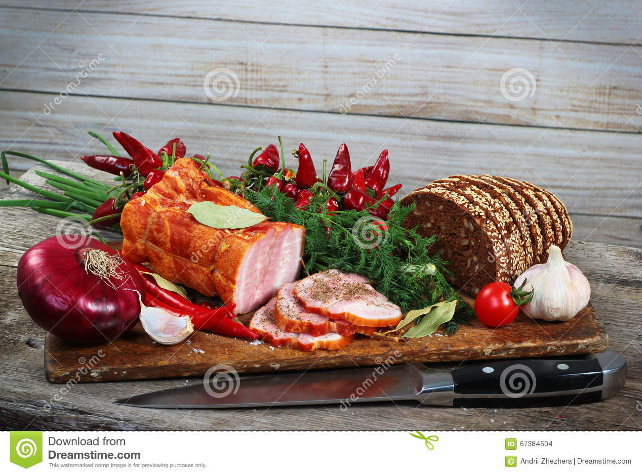Ham and bread sliced with knife. Green and red vegetables on chopping board