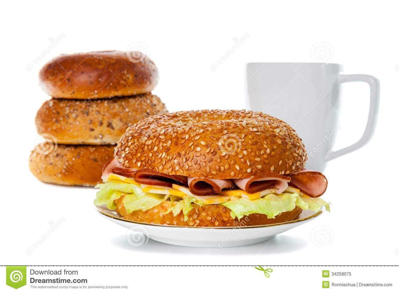 and cheese bagel sandwich on a plate with stacks of bagel and coffee ...