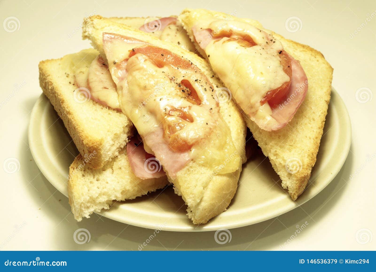 Ham, tomaten en de driehoeken van de kaastoost die op een plaat wordt gediend