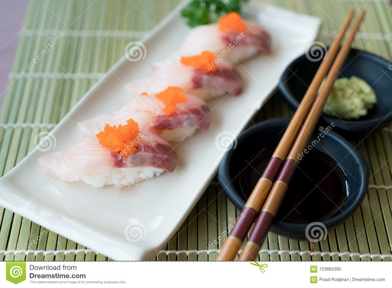 Hamachi Sushi On White Plate Along With Japanese Sauce And Green
