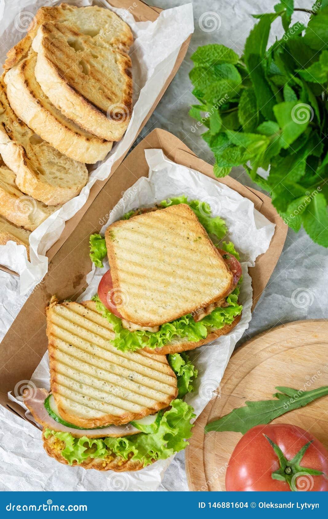 Hambrood met plantaardige salade en tomaat op een lijst en een document