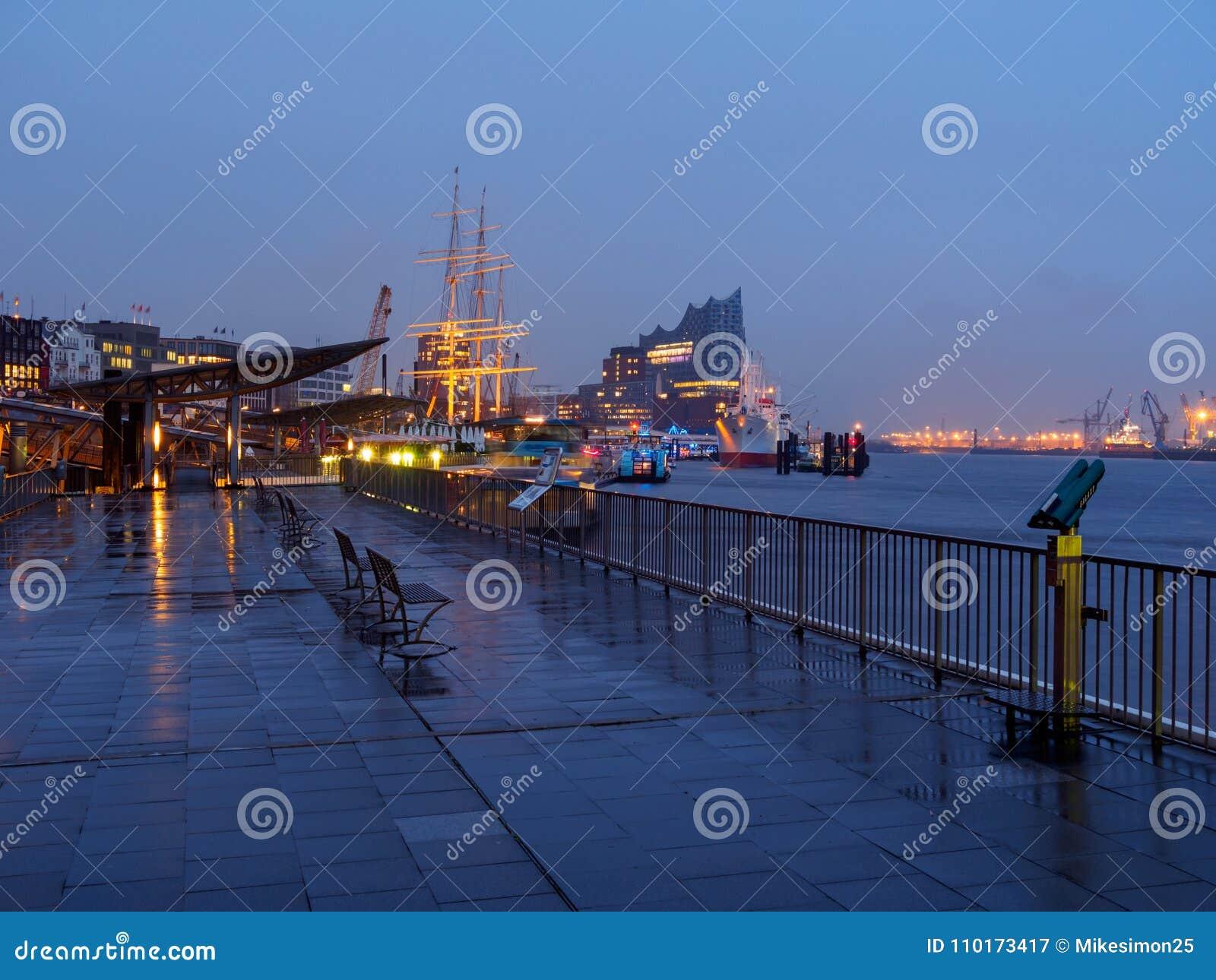 Hamburg, Deutschland - 4. April 2016: Verlassener Hafen von Hamburg an einem regnerischen Tag am Abend mit belichtetem Elbphilhar