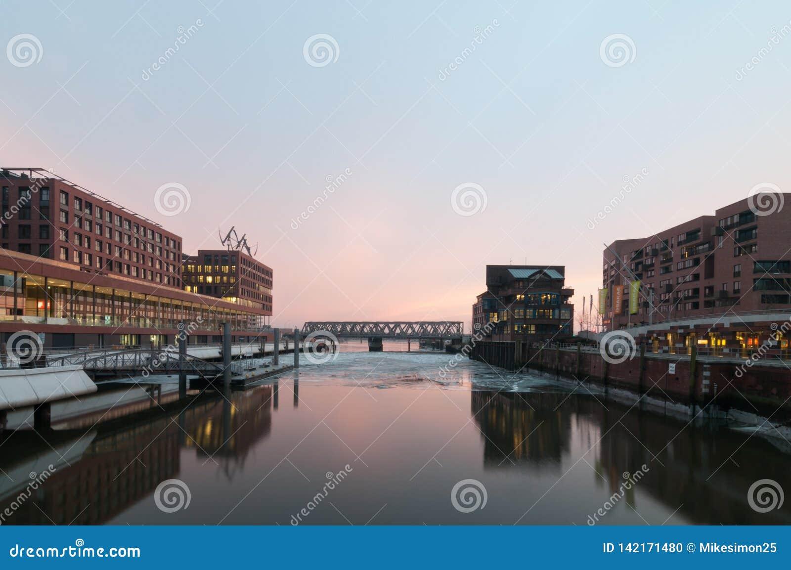Hamburg Tyskland - mars 04, 2014: Sikt från den Busan bron i Hafencity Hamburg på den Magdeburger bron i aftonen