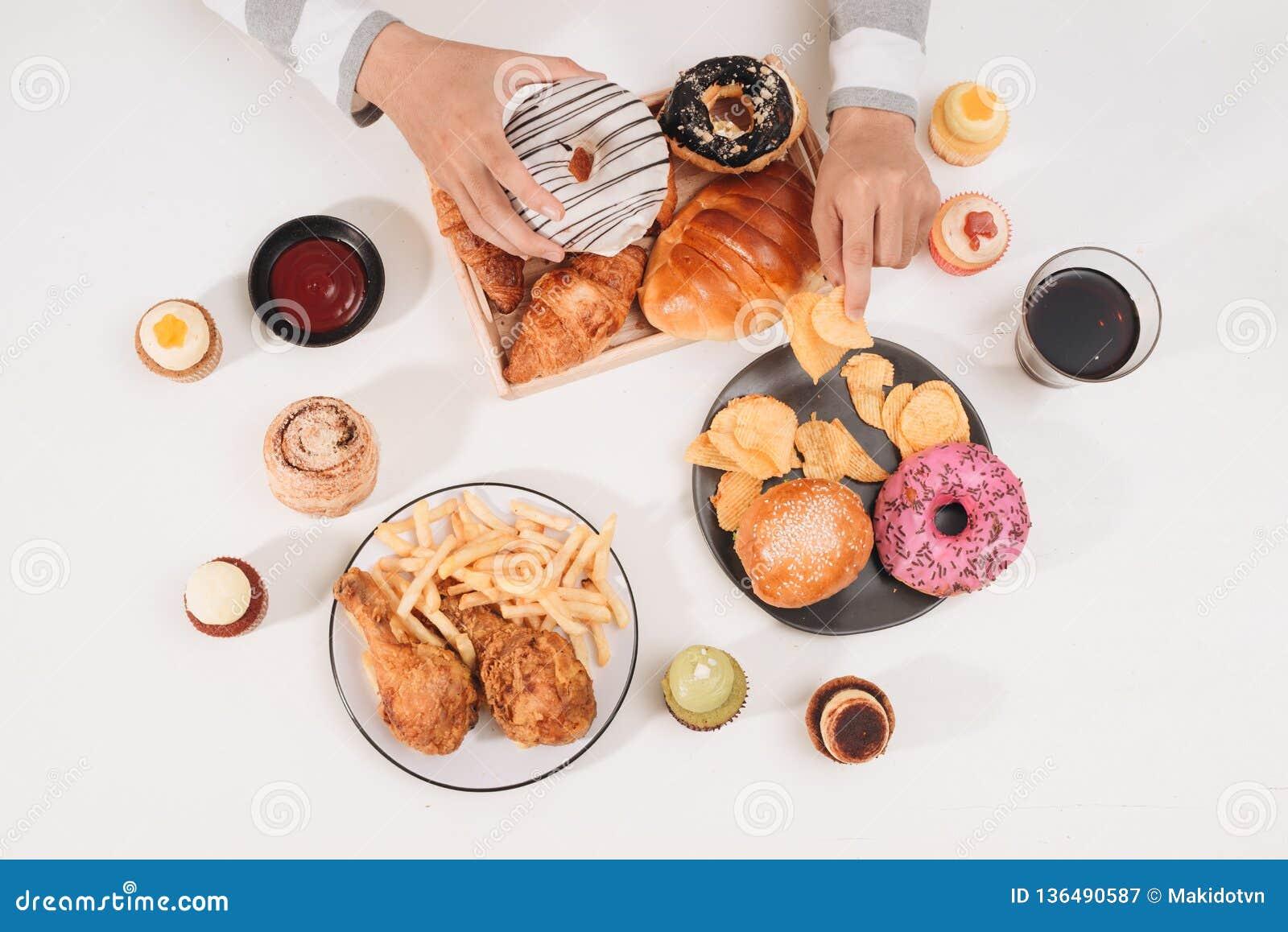 Hamburger de calorie avec des pommes frites, les gens mangeant à la table de café, déjeuner malsain