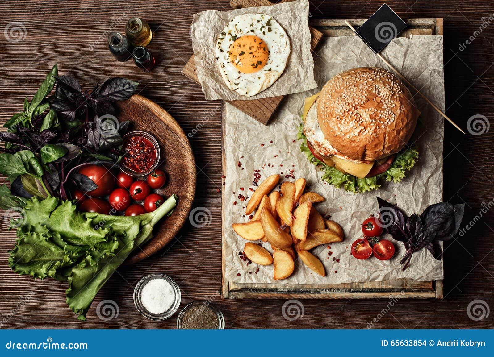 Hamburger de Veggie avec de la salade, la tomate et les fritures Fond en bois
