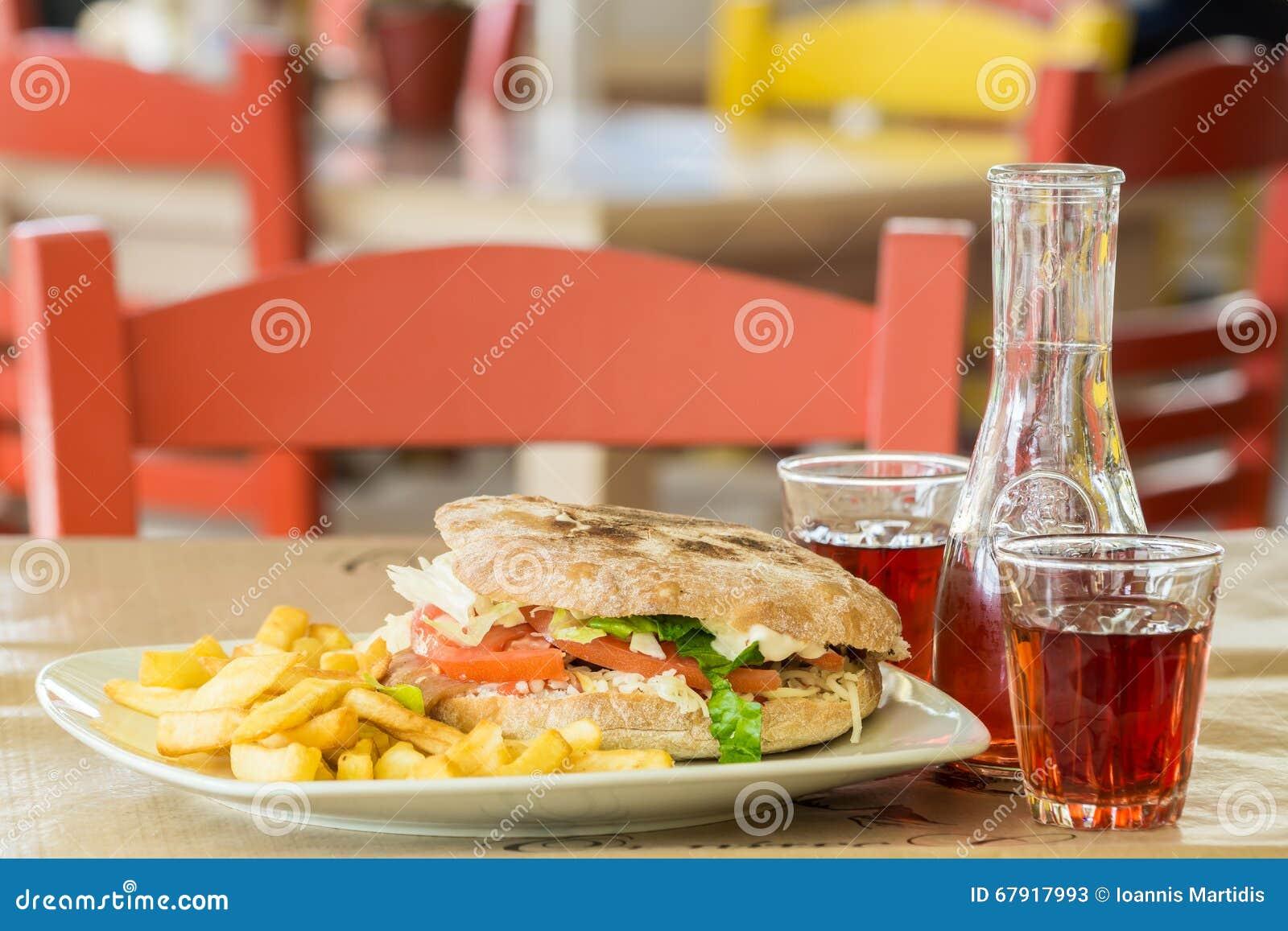 Hamburger des italienischen Brotes mit einem großen Steak Grafin und zwei Gläser Wein In der Taverne in Griechenland