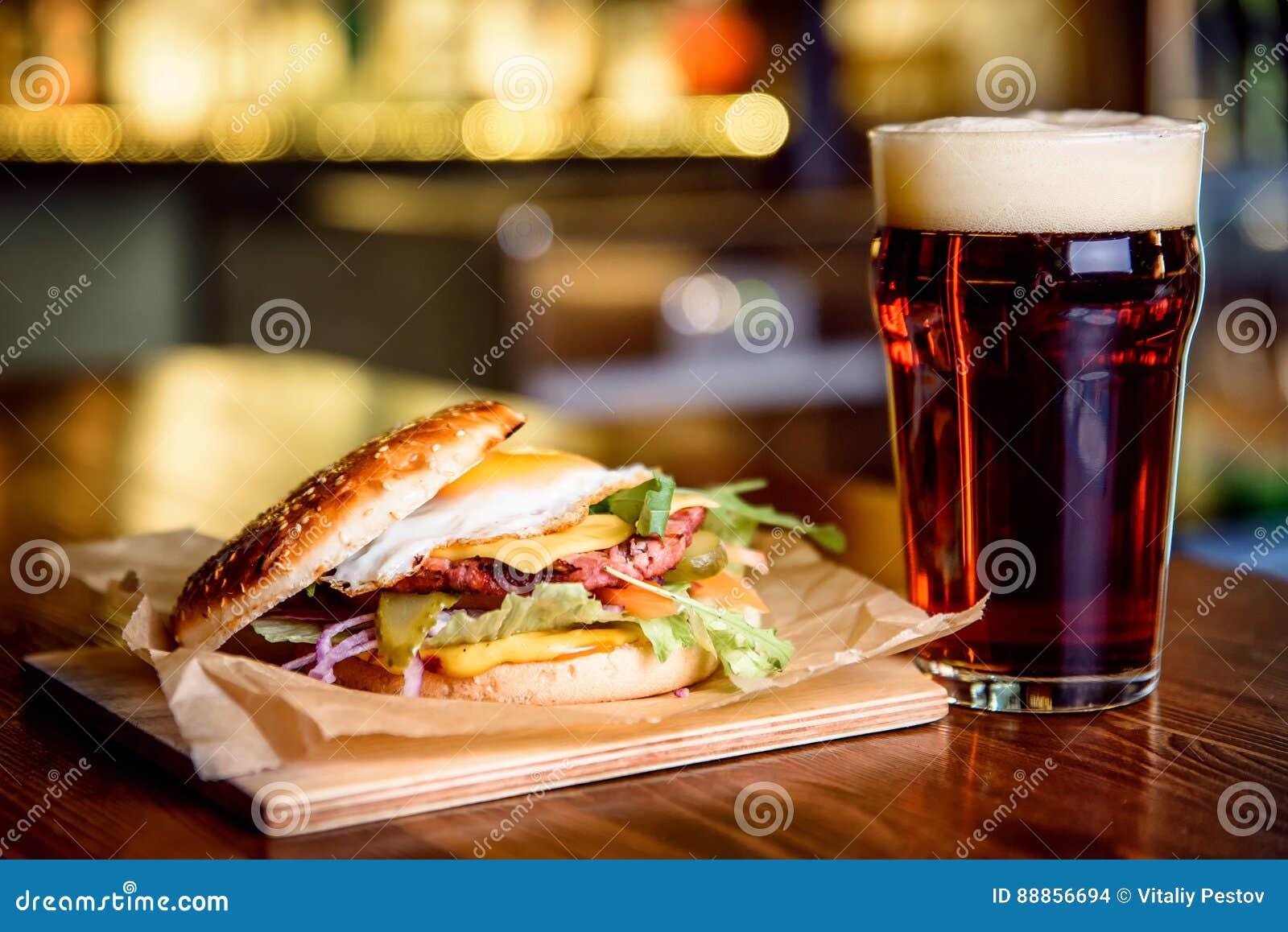 Hamburger en donker bier op een barachtergrond