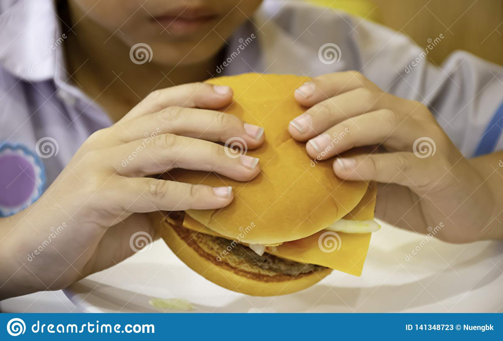 Hamburger fish and cheese in hand asia boy holding the eating