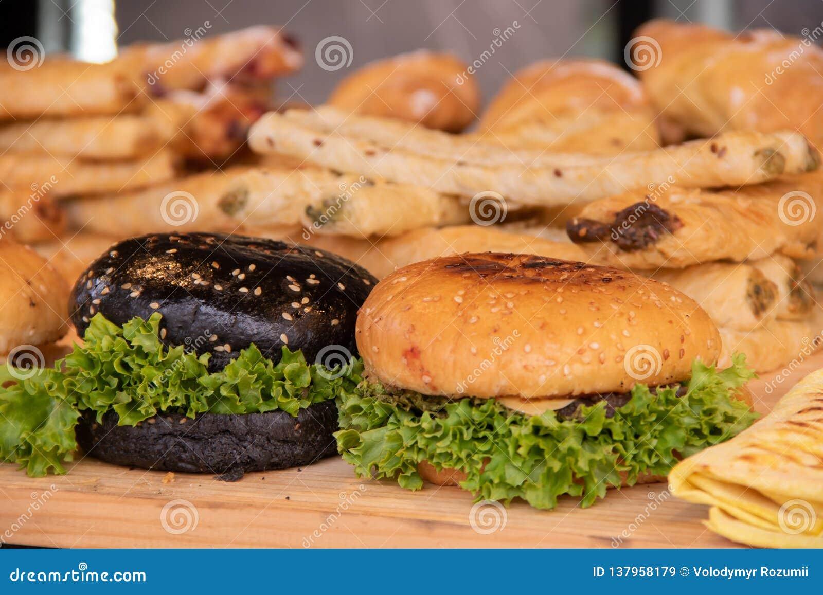 Hamburgery z mąką, mięsnymi cutlets i zieleniami białą i czarną, żadny uliczni karmowi festiwale