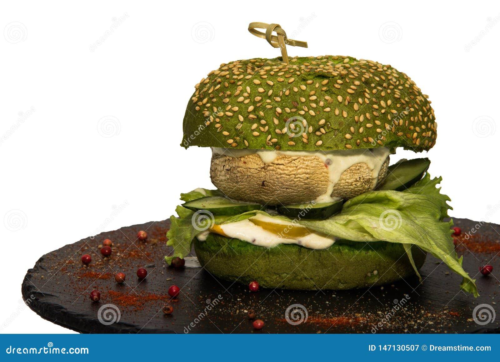 Hamburguer do vegetariano com uma folha da salada verde, do cogumelo, dos pepinos e do molho