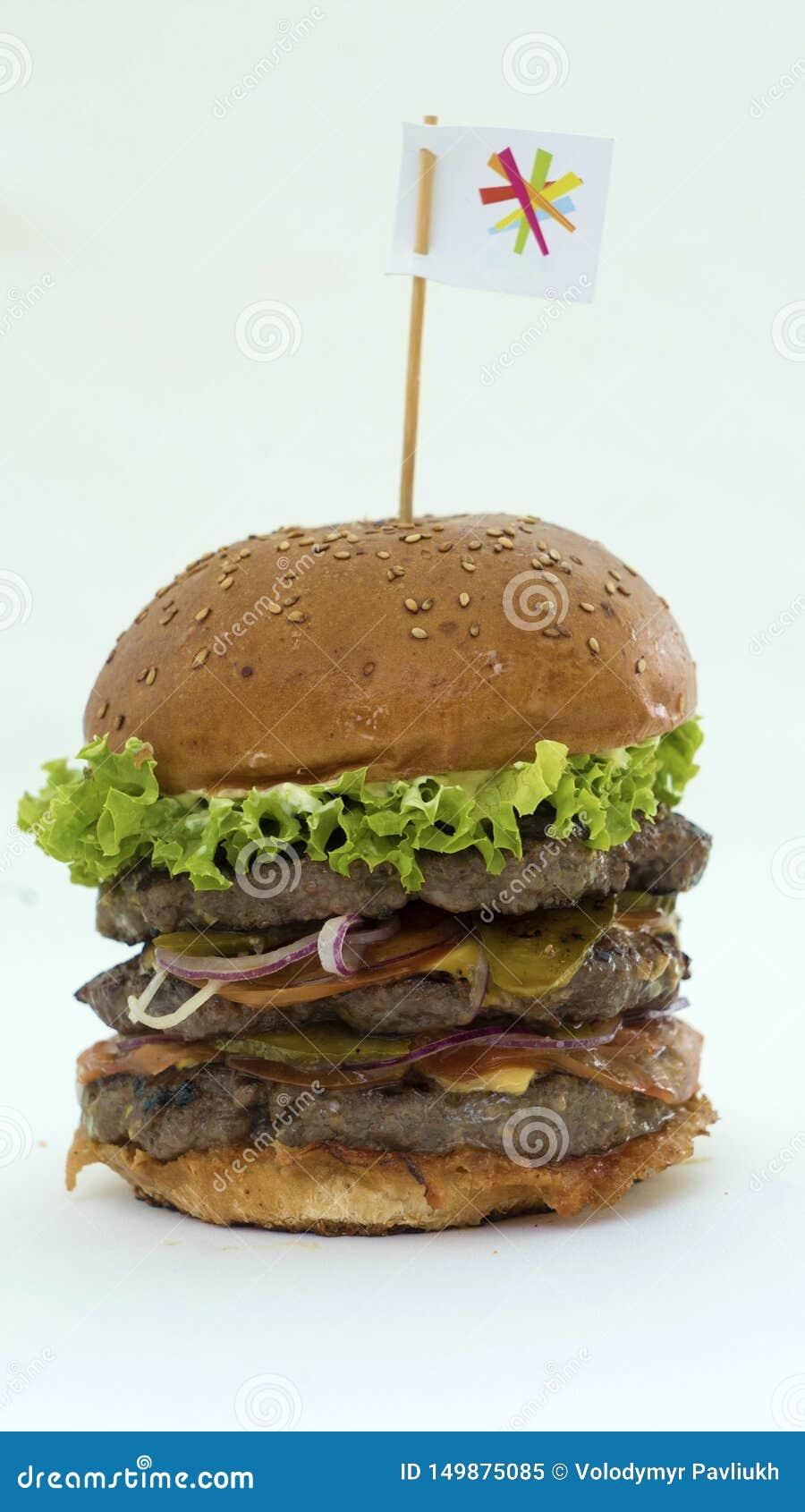 Hamburguer suculento com carne e os legumes frescos em um fundo branco, cozinhado com suas próprias mãos