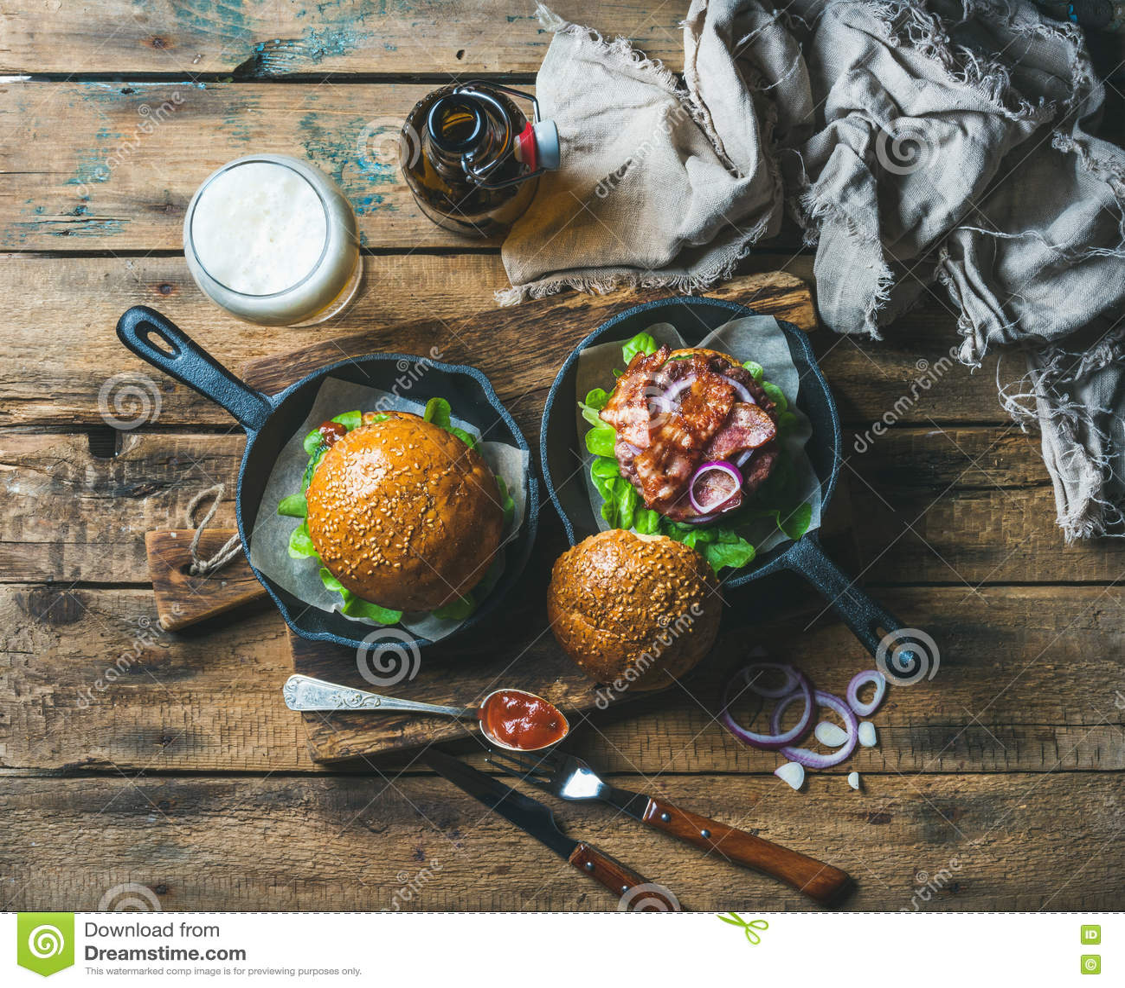 Hamburgueres caseiros da carne com anéis friáveis do bacon, da alface e de cebola