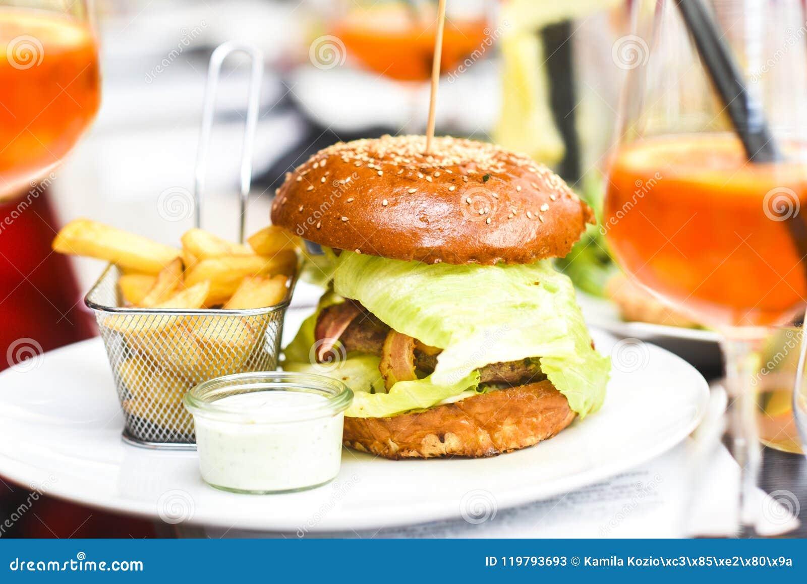 Hamburguesa con las fritadas en una placa en un restaura maravillosamente servido