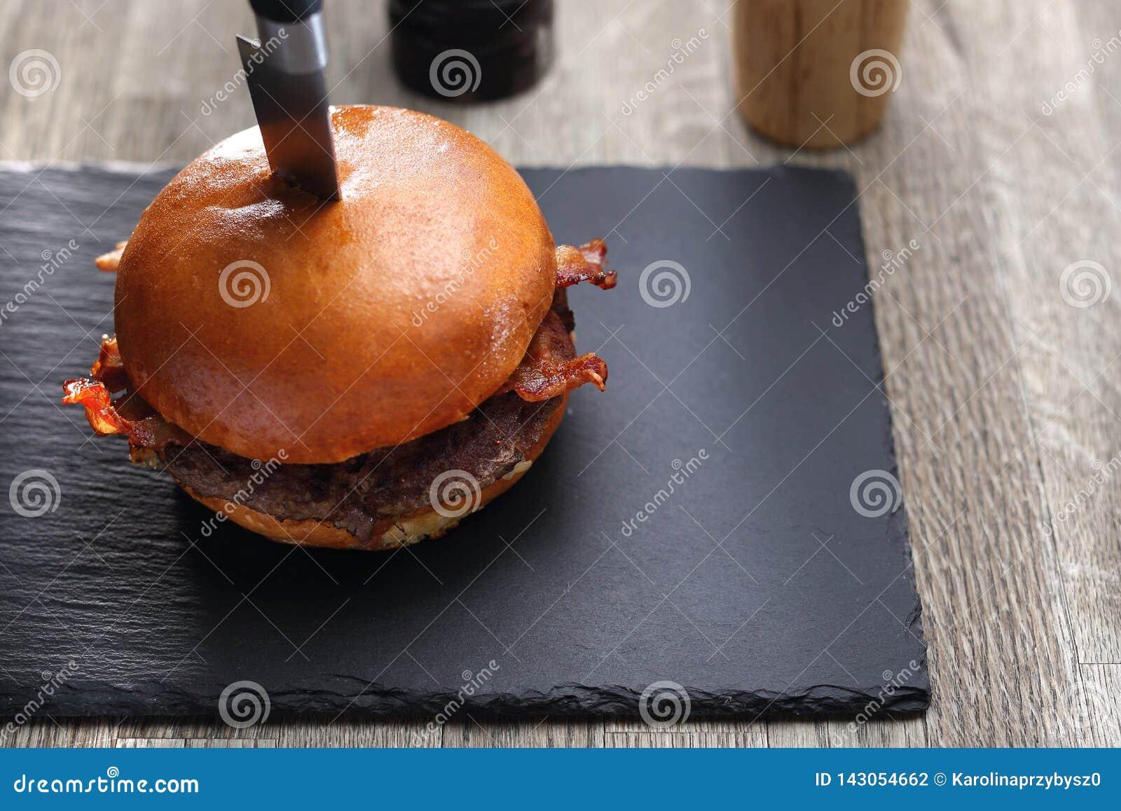Hamburguesa con tocino Chuleta asada a la parrilla de la carne de vaca en un bollo