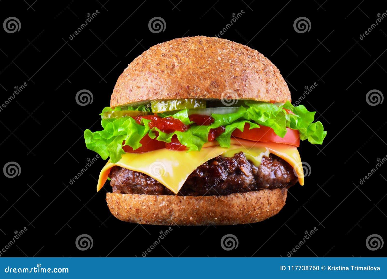 Hamburguesa o cheeseburger sabrosa grande aislado en fondo negro con la carne asada a la parrilla, queso, tomate, tocino, cebolla
