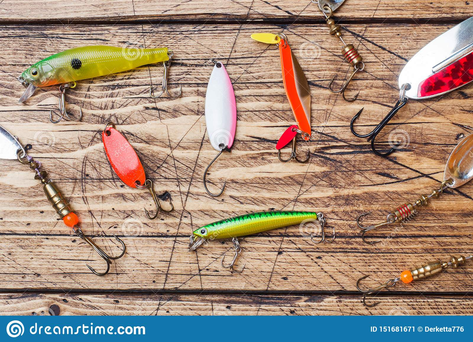 Hameçons et amorces dans un ensemble pour pêcher les poissons différents sur un fond en bois avec l espace de copie Configuration