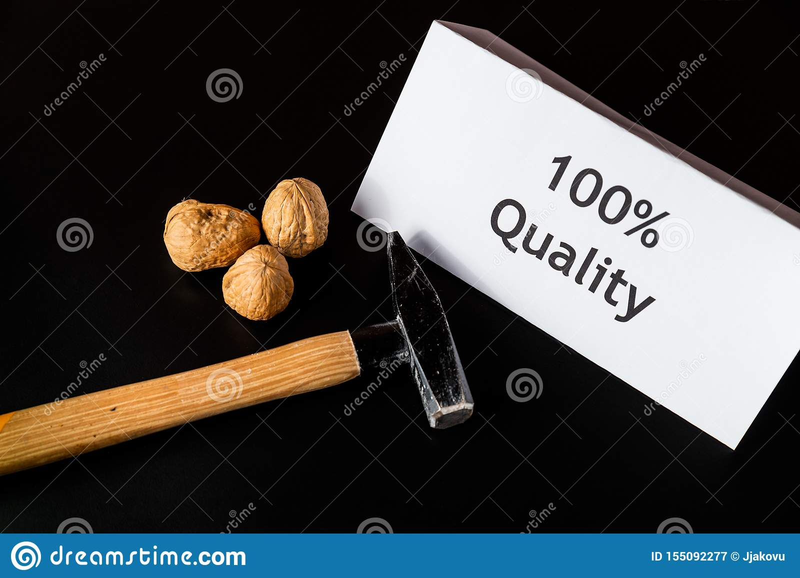 Hammer, three walnuts and paper/note `100  Quality` are on the black table/background. World Quality Day