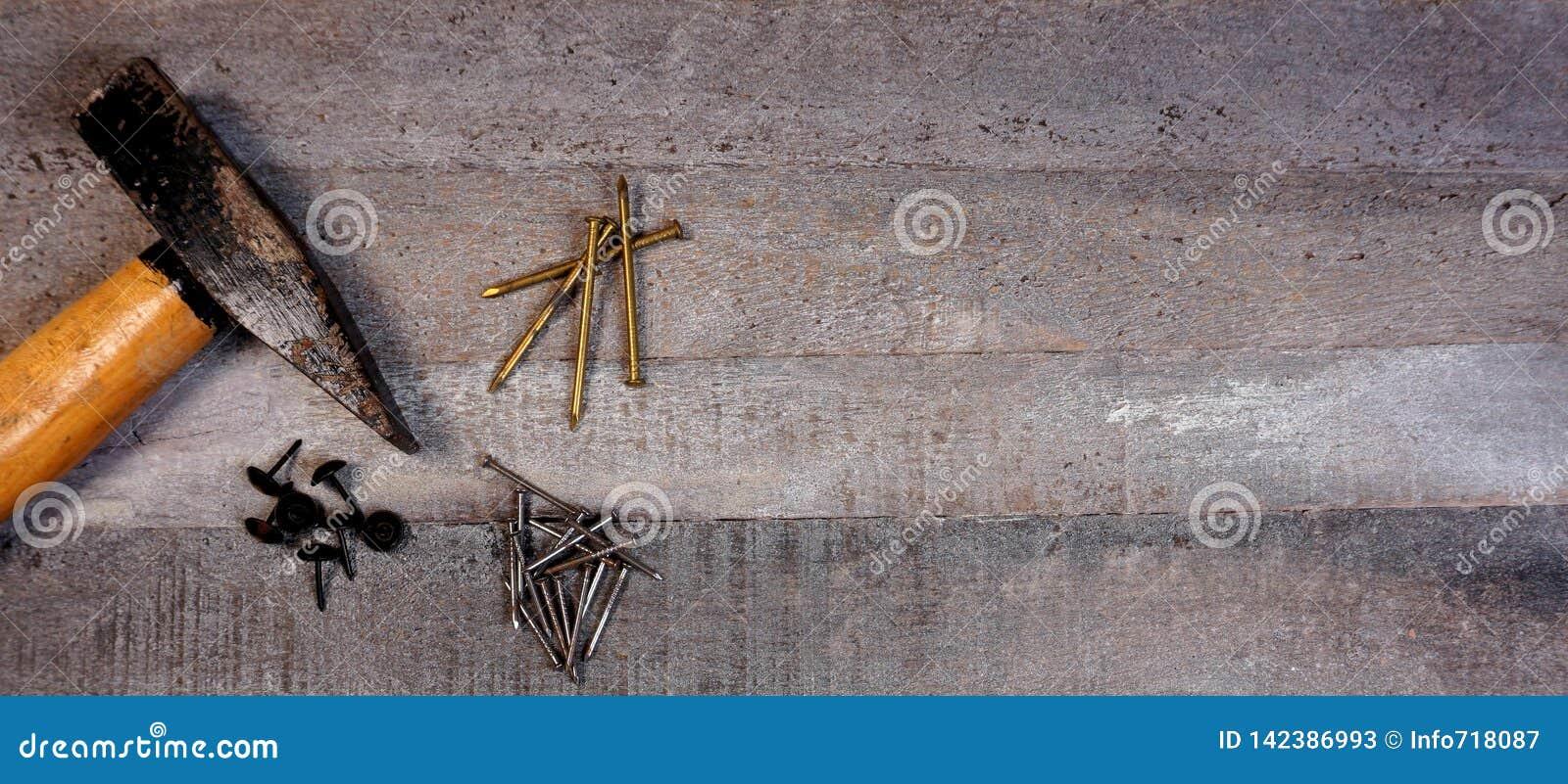 Hammer und Nägel auf natürlichem hölzernem Hintergrund mit Kopienraum für Ihren eigenen Text