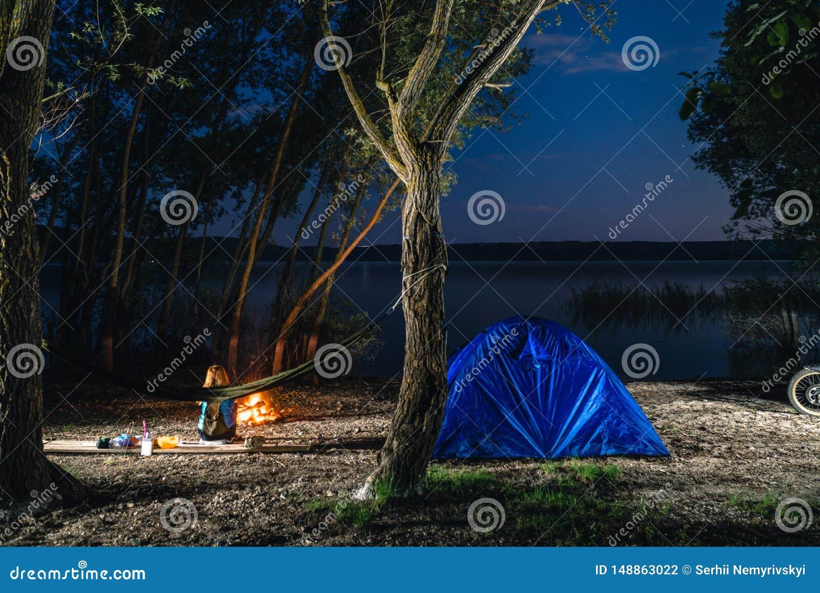Hammok и девушка сидят около костра Голубой располагаясь лагерем шатер загорелся внутрь Место для лагеря часов ночи Воссоздание и