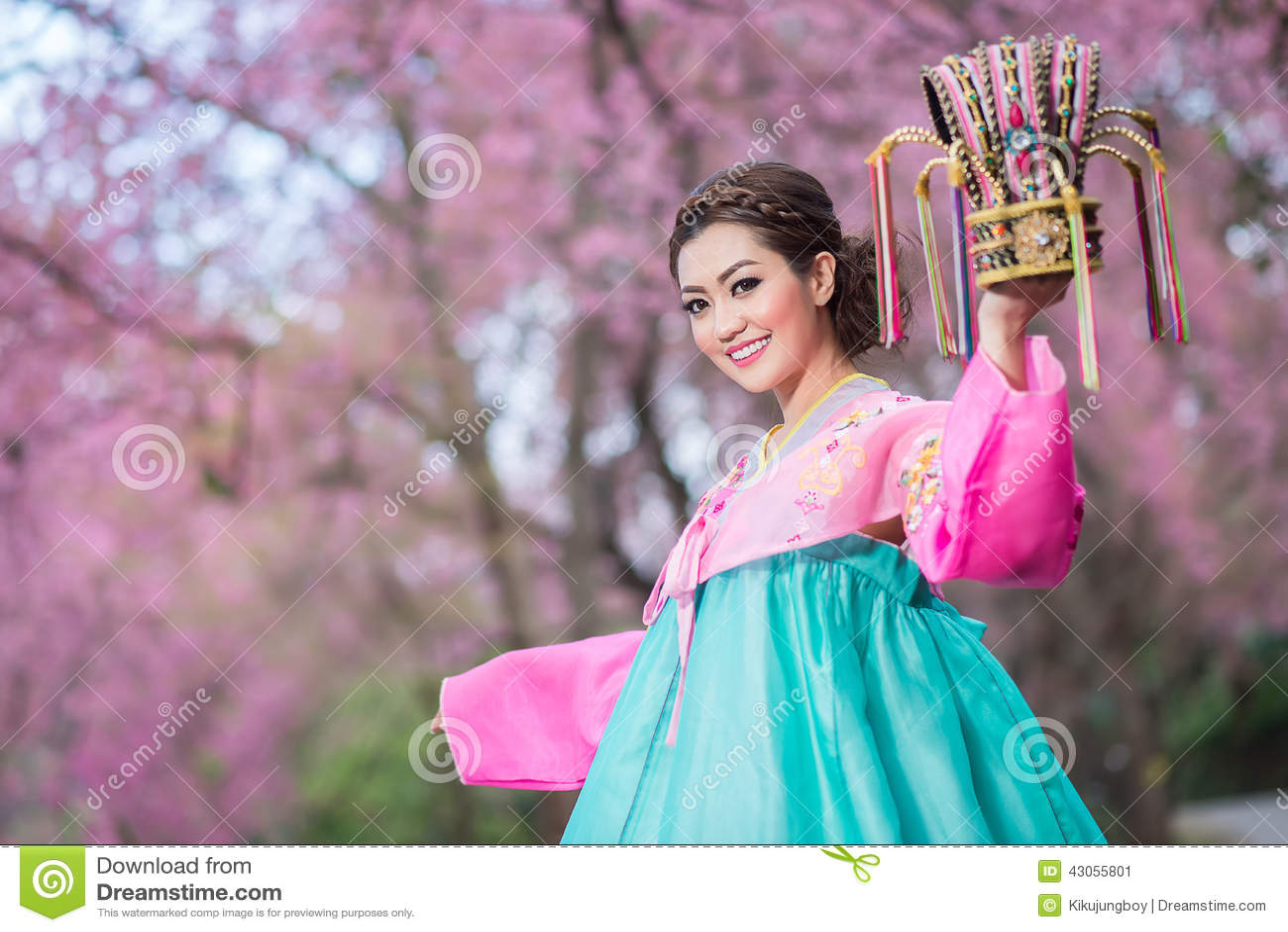 Hanbok: the traditional Korean dress and beautiful Asian girl holding crowd with sakura