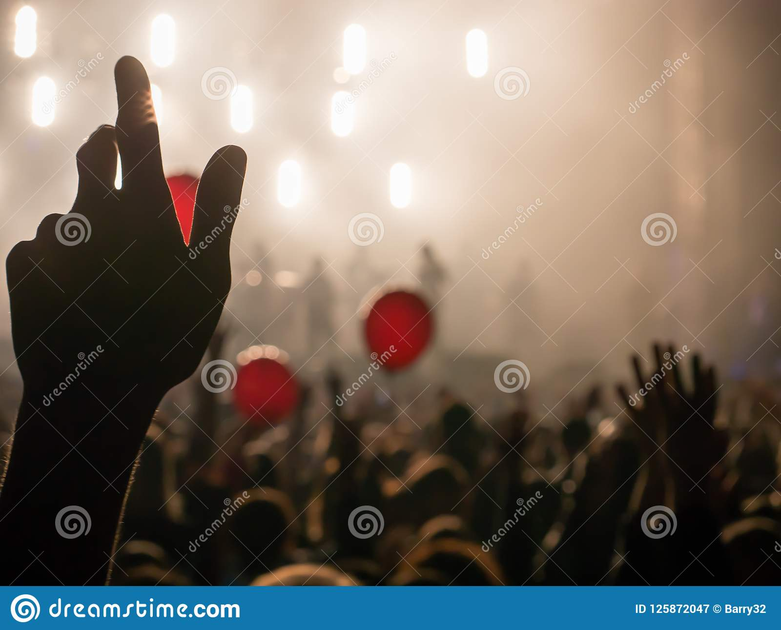 Hand in the air during rock concert silhouetted against bright lights