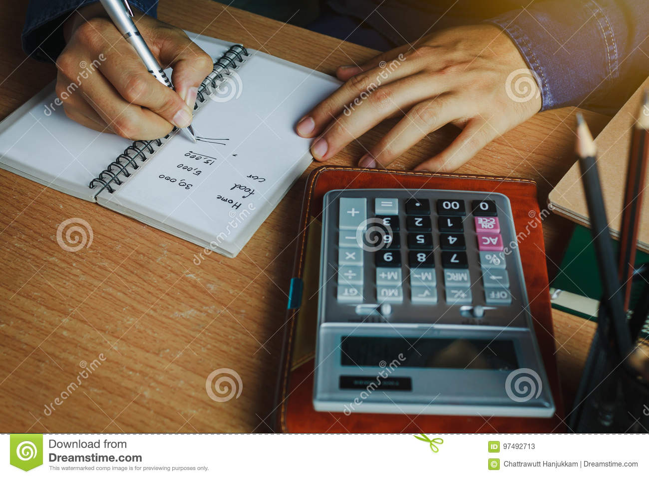 Hand Asian man calculate finances and accounting for monthly expenses / charges or cost