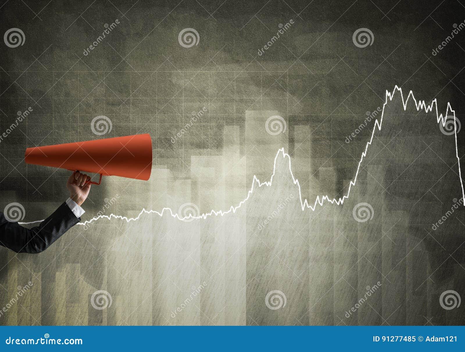 Hand av affärskvinnan som rymmer den röda pappers- trumpeten mot grafbakgrund