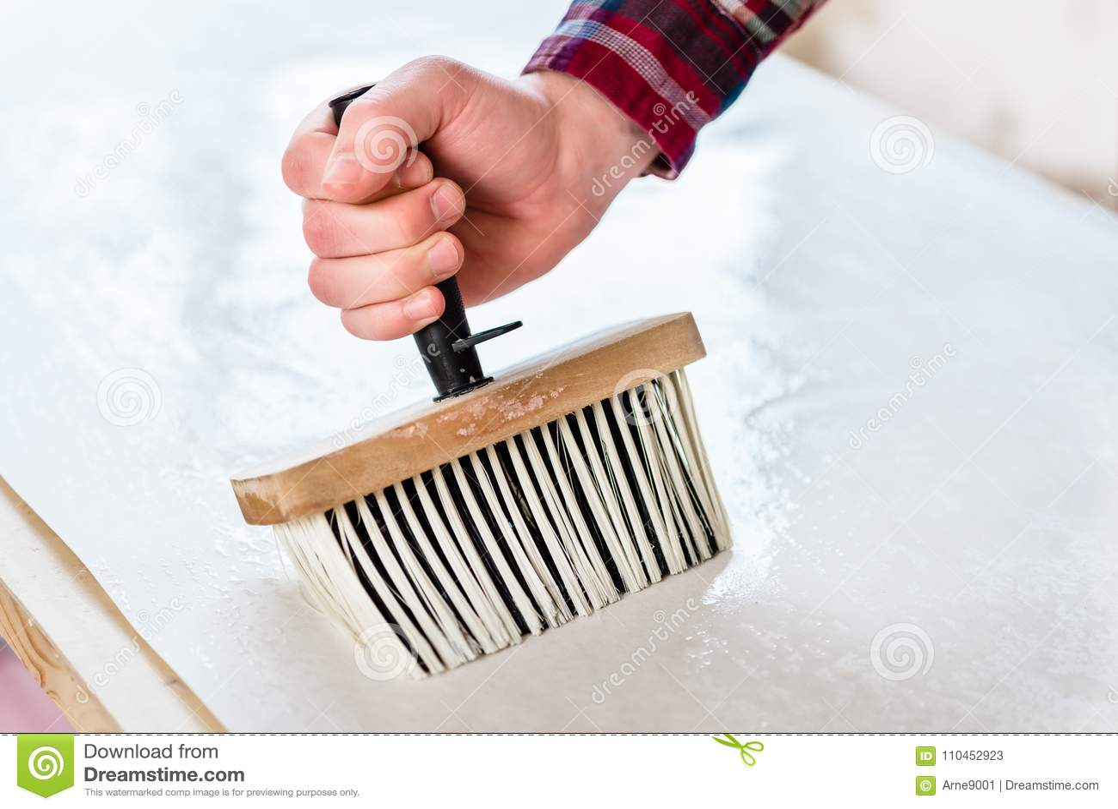 Hand av en man som rymmer en syntetisk borste, medan applicera deg