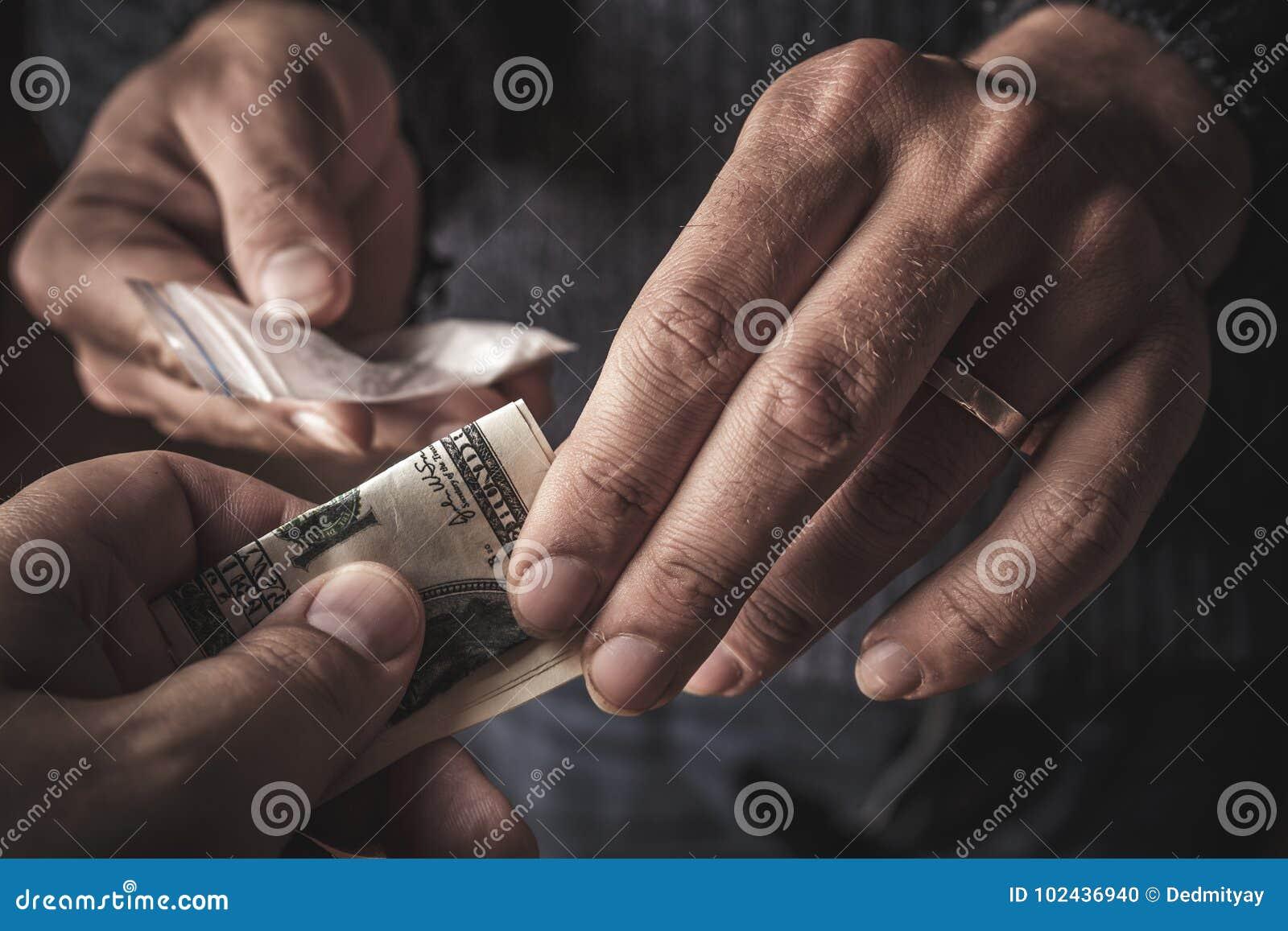 Hand av knarkaremannen med pengarköpandedosen av kokain eller hjältinnan eller ett annat narkotiskt preparat från knarklangare Dr