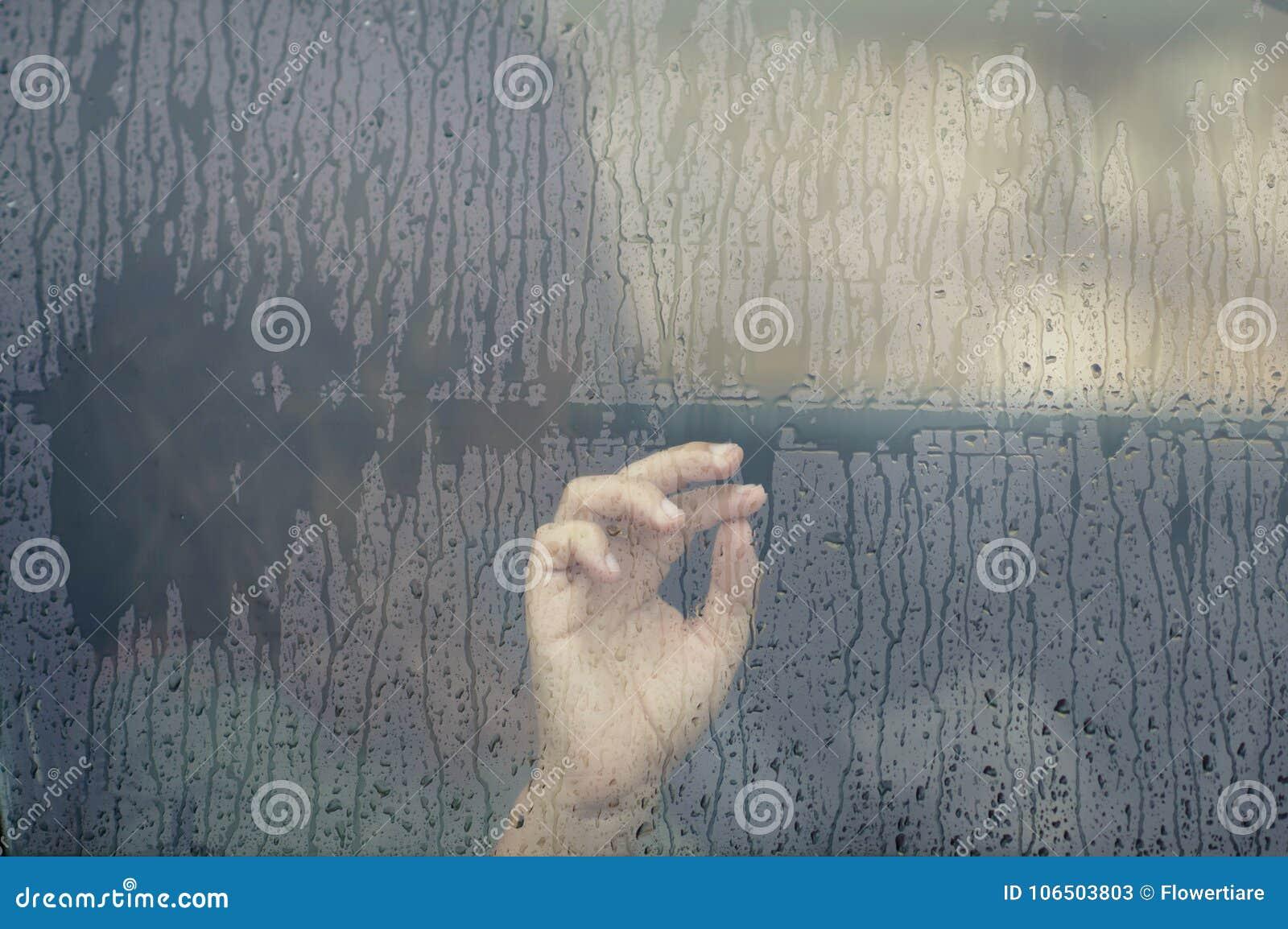 Hand av kvinnan i bilfönstret med regndroppe Ensamhet- och fördjupningsbegrepp