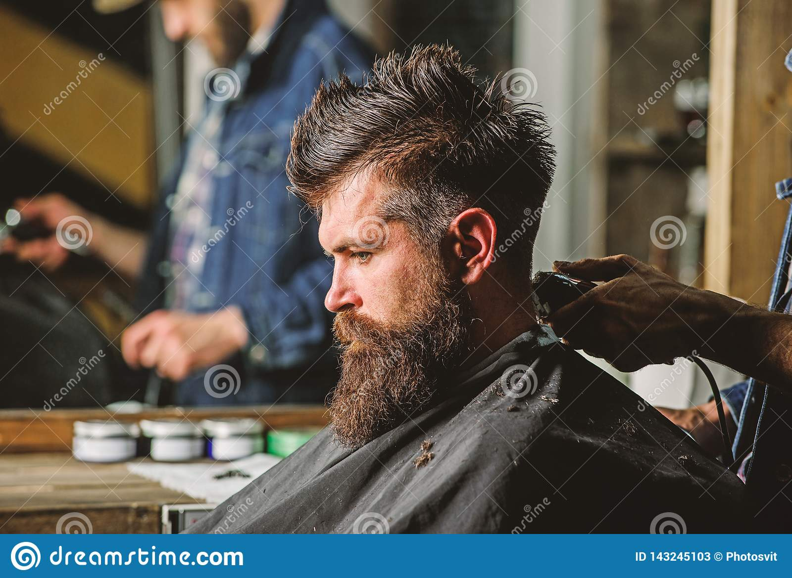 Hand of barber with hair clipper, close up. Hipster bearded client getting hairstyle. Barbershop concept. Man with beard