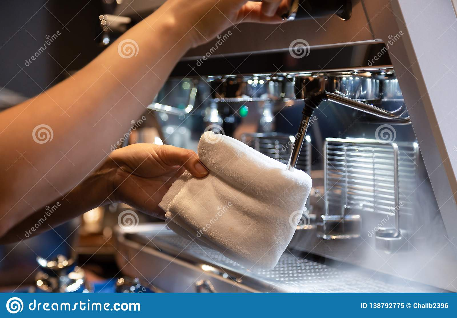 Hand of barista cleaning milk frother of coffee machine to be ready for milk frothing