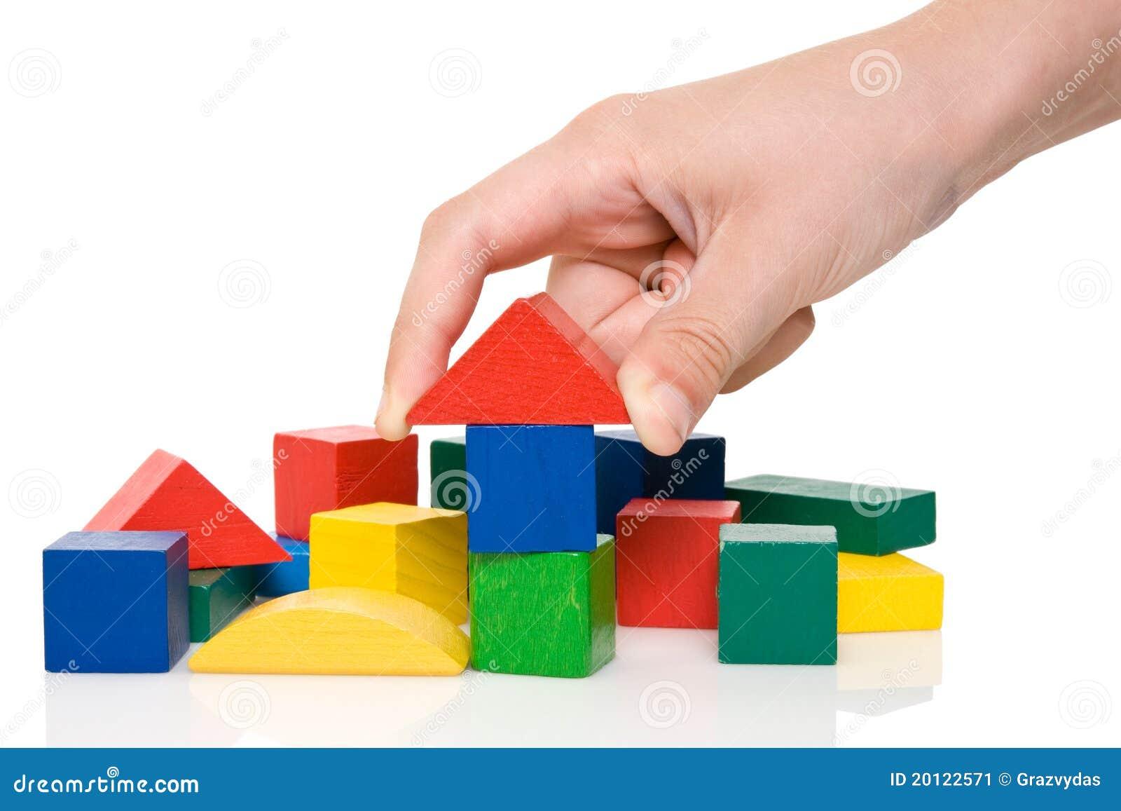 Hand bilden ein Gebäude von farbigen Blöcken.