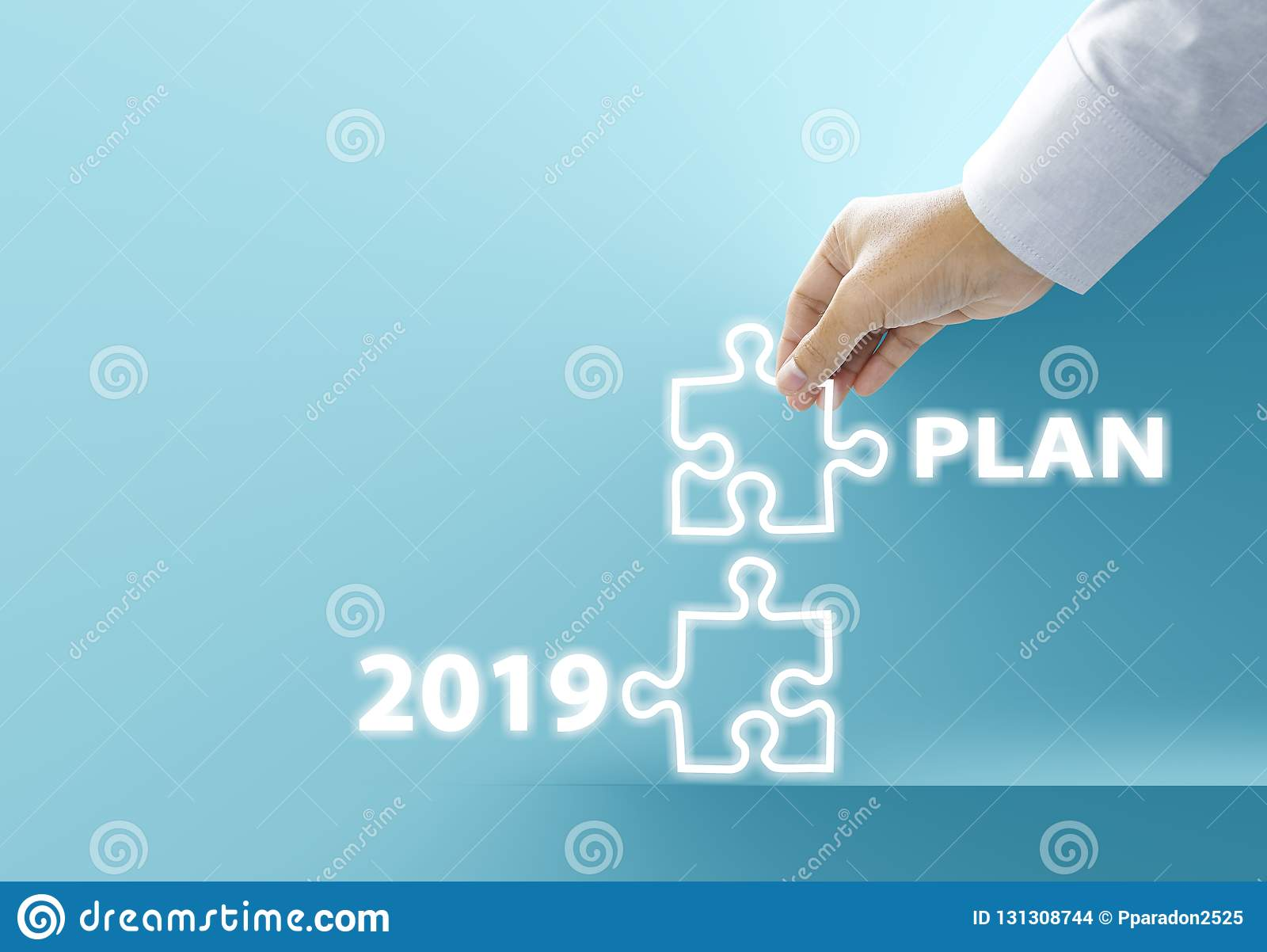 Hand of businessman connecting neon jigsaw puzzle with new year