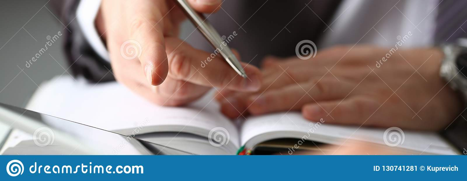 92867c38cd99 Hand of businessman in suit filling and signing with silver pen partnership  agreement form clipped to pad closeup. Management training course some  important ...